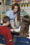 Teacher Helping Students In Classroom Stock Photos