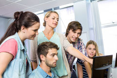 Teacher helping students in her class. Female computer teacher helping students in her class Stock Photography