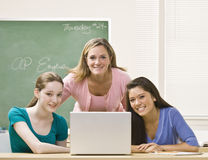 Teacher helping students on laptop Royalty Free Stock Photography