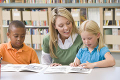 Teacher helping students with reading skills