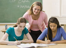 Teacher helping students study Stock Images