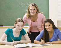Teacher helping students study. Teacher poses with her students in the classroom Royalty Free Stock Image