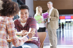 Teacher helping students studying in school hallway Royalty Free Stock Photography