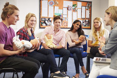 Teacher Helping Students Taking Childcare Course Stock Photo