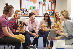 Teacher Helping Students Taking Childcare Course stock photos