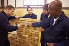 Teacher Helping Students Training To Be Builders Stock Image