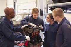 Teacher Helping Students Training To Be Car Mechanics Stock Photo