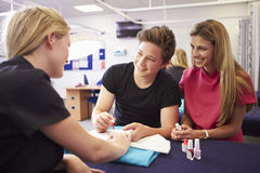 Teacher Helping Students Training To Become Beauticians Stock Photos