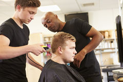 Teacher Helping Students Training To Become Hairdressers Stock Image