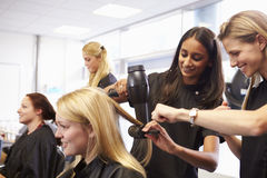 Teacher Helping Students Training To Become Hairdressers Stock Photography