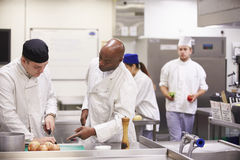 Teacher Helping Students Training To Work In Catering Stock Images