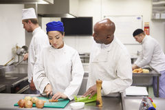 Teacher Helping Students Training To Work In Catering Royalty Free Stock Photography
