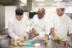 Teacher Helping Students Training To Work In Catering Stock Photos