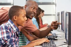Teacher Helping Students Working At Computers In Classroom Stock Photos