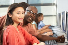 Teacher Helping Students Working At Computers In Classroom. Looking At Camera Smiling Royalty Free Stock Images
