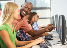 Teacher Helping Students Working At Computers In Classroom Stock Photo