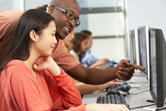 Teacher Helping Students Working At Computers In Classroom Stock Photography