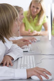 Teacher helping students working on computers in school computer lab Royalty Free Stock Photo