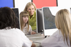 Teacher helping students working on computers in school computer lab Stock Photos