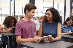 Teacher helping teenage schoolboy with tablet computer royalty free stock photos