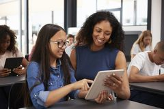 Teacher helping teenage schoolgirl with tablet computer Stock Images