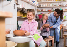Teacher helping teenagers at making pottery during arts and crafts class. Positive female teacher helping teenagers at making pottery during arts and crafts royalty free stock photo