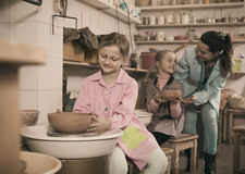 teacher helping teenagers at making pottery during arts and crafts class royalty free stock photo