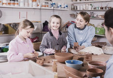 Teacher helping teenagers at making pottery during arts and craf. Smiling american  female teacher helping teenagers at making pottery during arts and crafts Royalty Free Stock Photos