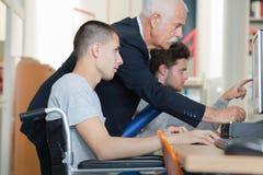 Teacher helping wheelchair student Stock Photo