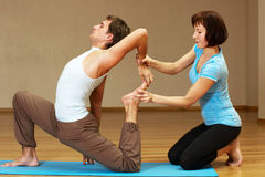 Teacher helping with yoga pose. Indoors Royalty Free Stock Image