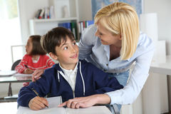 Teacher with kid in classroom Royalty Free Stock Photos