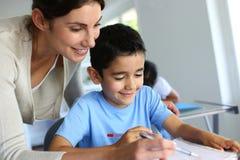 Teacher helping young boy writing Stock Image