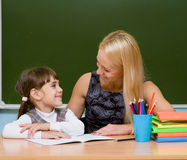 Teacher helping young girl with writing lesson.  Royalty Free Stock Images