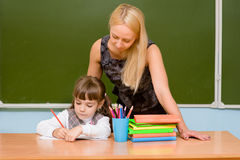Teacher helping young girl with writing lesson Royalty Free Stock Photography