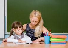 Teacher helping young girl with writing lesson Royalty Free Stock Photo