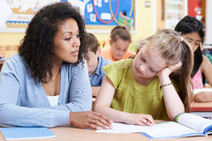 Teacher Helps Female Elementary School Pupil With Problem Stock Photo