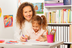 Teacher helps her pupil to write at a copybook. Teacher helps her pupil to write in a copybook at a school desk Stock Image