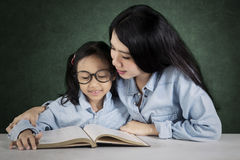 Teacher helps her student to read a book Stock Photography