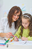 Teacher helps little girl Stock Photo