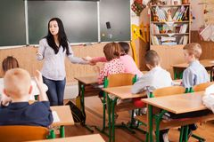 Teacher helps the pupil. Gives him a pencil to draw Stock Image
