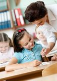 Teacher helps pupils to do the task Stock Image
