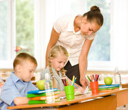 Teacher helps the schoolkids with schoolwork in classroom Royalty Free Stock Photos