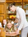 Teacher helps the schoolkids with schoolwork in classroom Stock Photos