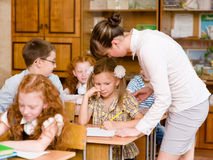 Teacher helps the schoolkids with schoolwork in classroom Stock Images