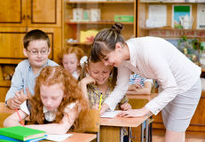 Teacher helps the schoolkids with schoolwork in classroom Stock Image