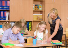 Teacher helps the schoolkids with schoolwork in classroom Stock Photography