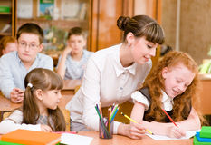 Teacher helps the student with schoolwork in  classroom Stock Photos