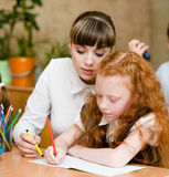 Teacher helps the student with schoolwork in school classroom Royalty Free Stock Photography