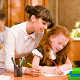 Teacher helps the student with schoolwork in school classroom.  Stock Photos