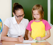 Teacher helps the student with schoolwork in school classroom Royalty Free Stock Photos